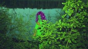 Η πράσινη μάγισσα προκύπτει από τους θάμνους στην ακτή της λίμνης στο σούρουπο και τα προσεκτικά βλέμματα γύρω απόθεμα βίντεο