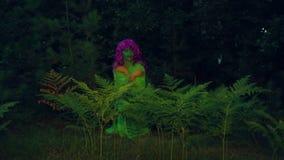 Η πράσινη μάγισσα προκύπτει από το αλσύλλιο της φτέρης και χαμογελά μυστιριωδώς απόθεμα βίντεο