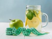 Η πράσινη μετρώντας ταινία, η πράσινη Apple και μια κούπα του λεμονιού και της μέντας ποτίζουν σε έναν ξύλινο πίνακα Στοκ εικόνες με δικαίωμα ελεύθερης χρήσης