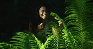 Η πράσινη σύνθεση της εύθυμης αφροαμερικανίδας γυναίκας με τις πράσινες σκιές κραγιόν και ματιών που ψεκάζουν τη φτέρη με απόθεμα βίντεο