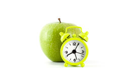 Η πράσινη Apple και ένα ξυπνητήρι Στοκ Φωτογραφίες
