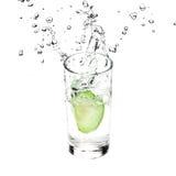 Η πράσινη Apple που πέφτουν στο γυαλί με το καθαρό νερό στο άσπρο υπόβαθρο Στοκ φωτογραφίες με δικαίωμα ελεύθερης χρήσης