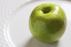 Η πράσινη Apple στο άσπρο πιάτο Λαμπρός οργανικός στενός επάνω Γιαγιάδων Σμίθ Στοκ εικόνες με δικαίωμα ελεύθερης χρήσης