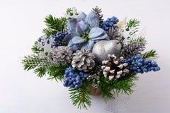 Η πρασινάδα Χριστουγέννων με το ασήμι ακτινοβολεί ντεκόρ και μπλε μετάξι poins Στοκ Εικόνες