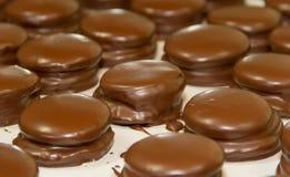 Η προετοιμασία των alfajores dulce de leche έλουσε στη σοκολάτα στοκ φωτογραφίες