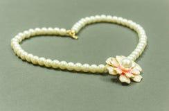 Η προθήκη του ελεφαντόδοντου χρωμάτισε το περιδέραιο πολύτιμων λίθων με διαμορφωμένο το λουλούδι κρεμαστό κόσμημα και τα σκουλαρί στοκ εικόνα