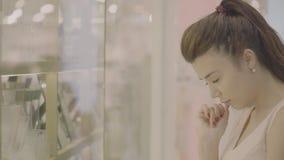 Η προθήκη του μαγαζί λιανικής πώλησης και η γυναίκα επιλέγουν τα αγαθά απόθεμα βίντεο