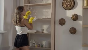 Η προκλητική γυναίκα στα κίτρινα λαστιχένια γάντια αφαιρεί τη σκόνη prom το ράφι σε σε αργή κίνηση, η νέα γυναίκα καθαρίζει το σπ φιλμ μικρού μήκους