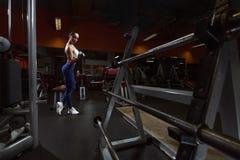 Η προκλητική γυναίκα brunette ικανότητας κάνει τις μπούκλες δικέφαλων μυών με τους αλτήρες στη γυμναστική στοκ εικόνες