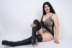 Η προκλητική επικίνδυνη γυναίκα brunette στις υψηλές μπότες μηρών μαγιό και δέρματος λεοπαρδάλεων με το σκελετό βάζει τακούνια στ στοκ φωτογραφία