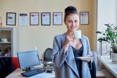 Η προκλητική προκλητική επιχειρησιακή γυναίκα πίνει τον καφέ στο γραφείο στοκ φωτογραφίες