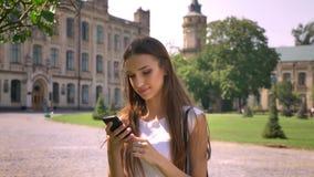 Η προκλητική κυρία στέκεται στο πάρκο στην ημέρα, διαβάζοντας το μήνυμα στο smartphone, έννοια επικοινωνίας φιλμ μικρού μήκους