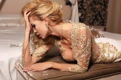 Η προκλητική γυναίκα με τα μακριά ξανθά μαλλιά φορά το κόσμημα δαντελλών luxurios το γαμήλια φόρεμα και Στοκ Εικόνες