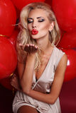 Η προκλητική γυναίκα με την ξανθή σγουρή τρίχα φορά το κομψό φόρεμα, κρατώντας πολλά κόκκινα μπαλόνια αέρα Στοκ Φωτογραφία