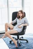 Η προκλητική καυκάσια γυναίκα με μακρυμάλλη έντυσε στο πουκάμισο πυτζαμών, καθμένος στην καρέκλα γραφείων στο σπίτι στοκ φωτογραφία με δικαίωμα ελεύθερης χρήσης
