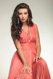 Η προκλητική νέα όμορφη γυναίκα στην κόκκινη συνεδρίαση φορεμάτων και θέτει Στοκ Εικόνα