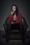 Η προκλητική υγρή γυναίκα στο πουλόβερ κάθεται στον καναπέ Στοκ εικόνα με δικαίωμα ελεύθερης χρήσης