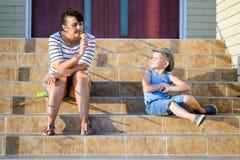 Η προσέχοντας μητέρα αγοριών τρώει τον κώνο παγωτού στα βήματα Στοκ Εικόνα