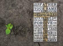 Η προσευχή Λόρδου ` s Ξύλινη χαρασμένη λέξη της προσευχής Λόρδου ` s στο επίγειο υπόβαθρο με πράσινες εγκαταστάσεις Στοκ Φωτογραφίες