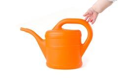 Η προσπάθεια μωρών να αρπάξουν ένα πορτοκαλί πότισμα μπορεί στο άσπρο υπόβαθρο στοκ φωτογραφία με δικαίωμα ελεύθερης χρήσης