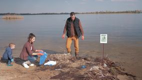 Η προστασία του περιβάλλοντος, αγόρι βοηθά τα οικογενειακά εθελοντικά ενεργά στελέχη να καθαρίσουν επάνω τη μολυσμένη παραλία ποτ απόθεμα βίντεο