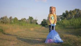 Η προστασία του περιβάλλοντος, ευτυχές μικρό κορίτσι τραβά μια μεγάλη τσάντα απορριμμάτων με τα σκουπίδια στο δρόμο σύμφωνα με το φιλμ μικρού μήκους