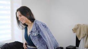 Η προσωπική γυναίκα στιλίστων συμβουλεύει στα νέα θηλυκά ενδύματα πελατών στο δωμάτιο στην ημέρα, που βοηθά να κάνει μια εικόνα απόθεμα βίντεο