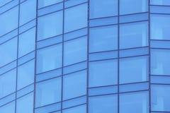 Η πρόσοψη γυαλιού ενός ουρανοξύστη με μια αντανάκλαση καθρεφτών των παραθύρων ουρανού στοκ φωτογραφία