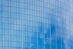 Η πρόσοψη γυαλιού ενός ουρανοξύστη με μια αντανάκλαση καθρεφτών των παραθύρων ουρανού στοκ εικόνες