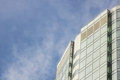 Η πρόσοψη γυαλιού ενός ουρανοξύστη με μια αντανάκλαση καθρεφτών των παραθύρων ουρανού στοκ φωτογραφία με δικαίωμα ελεύθερης χρήσης