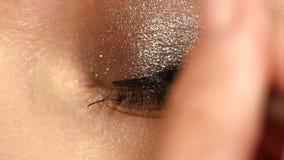 Η πρότυπη να ισχύσει eyeliner κινηματογράφηση σε πρώτο πλάνο στο μάτι, κλείνει επάνω φιλμ μικρού μήκους