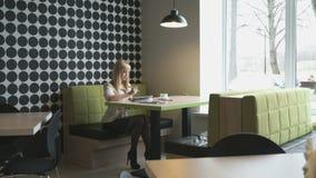Η πρότυπη συνεδρίαση κοριτσιών σε έναν καφέ γράφει το κείμενο μέσα καθημερινά φιλμ μικρού μήκους
