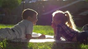 Η πρώτη αγάπη, το όμορφα μικρό παιδί και το κορίτσι που βρίσκονται στη χλόη και τις εικόνες άποψης σε ένα βιβλίο κατά τη διάρκεια απόθεμα βίντεο