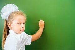 Η πρώτη μαθήτρια βαθμού έγραψε στον πίνακα με την κιμωλία στην τάξη Στοκ φωτογραφίες με δικαίωμα ελεύθερης χρήσης