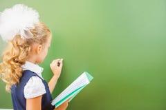 Η πρώτη μαθήτρια βαθμού έγραψε στον πίνακα με την κιμωλία στην τάξη Στοκ Φωτογραφία