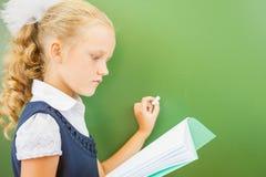 Η πρώτη μαθήτρια βαθμού έγραψε στον πίνακα με την κιμωλία στην τάξη Στοκ φωτογραφία με δικαίωμα ελεύθερης χρήσης