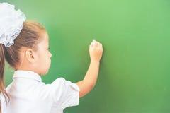 Η πρώτη μαθήτρια βαθμού έγραψε στον πίνακα με την κιμωλία στην τάξη Στοκ εικόνες με δικαίωμα ελεύθερης χρήσης