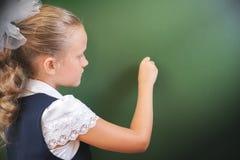 Η πρώτη μαθήτρια βαθμού έγραψε στον πίνακα με την κιμωλία στην τάξη Στοκ Εικόνες