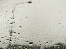 Η πτώση βροχής κοιτάζει μέσω του ανεμοφράκτη στοκ εικόνα