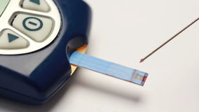 Η πτώση του αίματος επάνω στη λουρίδα δοκιμής του οργάνου ελέγχου γλυκόζης απόθεμα βίντεο