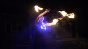 Η πυρκαγιά παρουσιάζει απόδοση Ο όμορφος αρσενικός εκτελεστής πυρκαγιάς που στροβιλίζει και που πετά επάνω το προσωπικό μπαστουνι απόθεμα βίντεο