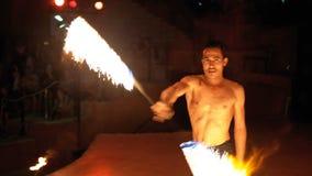 Η πυρκαγιά παρουσιάζει απόδοση στη σκηνή Ο νεαρός άνδρας που χορεύει με τους φλογερούς ανεμιστήρες σε μια νύχτα παρουσιάζει o φιλμ μικρού μήκους