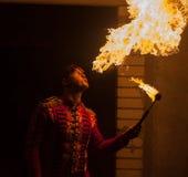 Η πυρκαγιά παρουσιάζει ότι ο καλλιτέχνης αναπνέει την πυρκαγιά στο σκοτάδι Στοκ Φωτογραφία