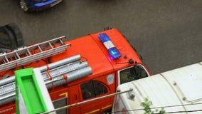 Η πυροσβεστική αντλία με τον ήχο αναλαμπτήρων ταξιδεύει γρήγορα τη διάσωση Ατύχημα από τη δυνατή βροχή φιλμ μικρού μήκους