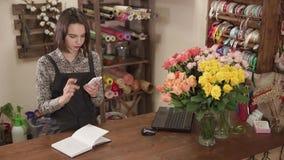 Η πωλήτρια του στούντιο λουλουδιών βασίζεται σε έναν υπολογιστή και ένα γράψιμο smartphone απόθεμα βίντεο
