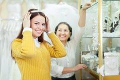 Η πωλήτρια βοηθά τη νύφη επιλέγει το νυφικό στεφάνι Στοκ εικόνα με δικαίωμα ελεύθερης χρήσης