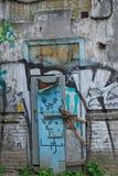 Η πόρτα και ο τοίχος ενός εγκαταλειμμένου σπιτιού χωρίς μισθωτές που χρωματίζεται Στοκ εικόνα με δικαίωμα ελεύθερης χρήσης