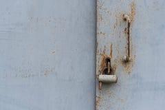 Η πόρτα που κλειδώνεται παλαιά με τα κρεμώντας υποστηρίγματα λουκέτων ανασκοπήσεις που τίθεν&tau Στοκ Εικόνες