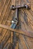 Η πόρτα που κλειδώνεται παλαιά με τα κρεμώντας υποστηρίγματα λουκέτων ανασκοπήσεις που τίθεν&tau Στοκ φωτογραφίες με δικαίωμα ελεύθερης χρήσης
