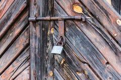 Η πόρτα που κλειδώνεται παλαιά με τα κρεμώντας υποστηρίγματα λουκέτων ανασκοπήσεις που τίθεν&tau Στοκ εικόνες με δικαίωμα ελεύθερης χρήσης